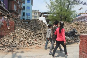 Kathmandu residents walk past a temple that collapsed in April 25 earthquake (Image by Ramesh Bhushal)