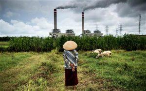 woman in a field walking towards a coal power plant
