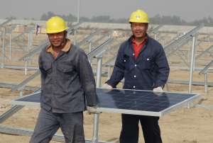 Chinese workers carry one of the 400,000 solar panels installed at the 100MW plant in Pakistan that could eventually be scaled up to 1,000MW, which would make it one of the world's largest (Image by Quaid-e-Azam Solar Power (Pvt.) Limited)