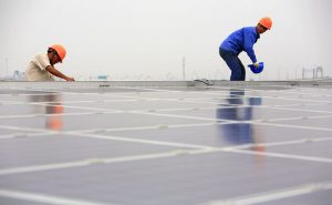 Workers install solar panels in Shanghai. China will need to raise the share of renewables in its energy mix to curb coal and peak CO2. (Image by Jiri Rezac/The Climate Group)