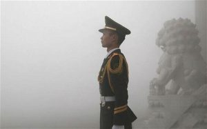 A Chinese soldier stands guard in central Beijing. Persistent smog over several days has triggered the city's first ever air quality 'red alert