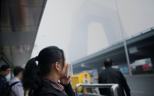 woman looks over air pollution in Beijing while wearing a mask