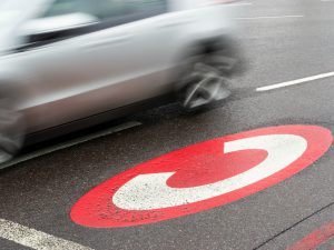 car zooms past road markings for London's congestion charge, a policy that has had mixed environmental results