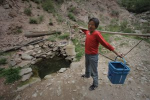 A woman collects water from a spring in a valley outside her village of Houjialiang in northwestern China, where coal mining has poisoned local rivers and streams (Image by Qiu Bo / Greenpeace)