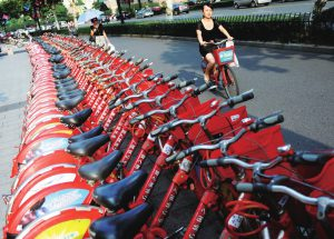 Red hire scheme bikes racked up outside a Hangzhou metro station