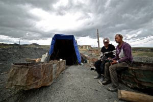 two men sit by the abandoned Nilaikh coal mine near Ulan Bator