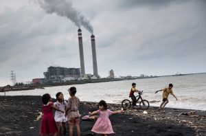 Children play by the beach near a coal power plant in Jepara, Central Java, Indonesia, oblivious to the possible threats to their health. The country is currently rolling back its commitment to reduce fossil fuel subsidies. (Image by Kemal Jufri / Greenpeace)