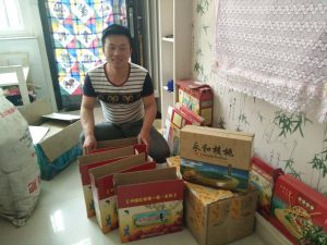Liu Dongdong, one of China's new rural e-commerce entrepreneurs, is pictured with boxes of red dates