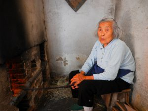 woman sitting down coal burning in Beijing