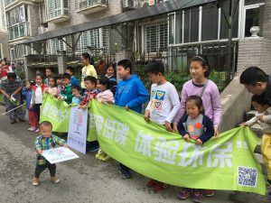 Children hold a banner outside the home of Helen Ni in Shanghai. The roof shading the patio is covered with solar panels. (Image: Helen Ni)
