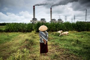 woman stands in front of coal power plant