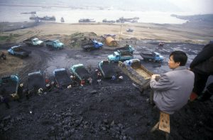 Mengfa Coal Company trucks and tractors deposit large piles of coal by the bank of the Ulan Moron River. (Image: Alamy)