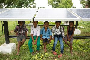 Children sit under solar panels in India (Image by Greenpeace)