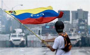 A protester waves a Venezuelan flag before the Venezuelan National Guard in May 2017 (Image: Efecto Eco)