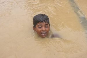 A boy swims through a flooded street in Ramgaduwa in southern Nepal (Image: Munna Saraff)