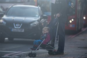 A young child is pushed in a pram across a busy road in London (Image:Elizabeth Dalziel/Greenpeace)