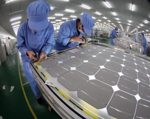Solar powered photovoltaic cells are assembled by workers at a factory in Dezhou, Shandong province (Image: Alamy)