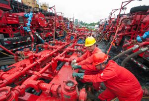 Workers of a subsidiary of Sinopec, China's largest oil refiner, disassemble facilities after a trial operation in Chongqing, south-west China (Image: