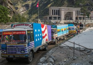 Trucks entering Nepal from China at Rasuwa Gadhi inland port. The Chinese Customs and Immigration office is in the background. (Images: Nabin Baral)
