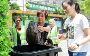 Volunteers help Shanghai residents navigate new waste separation rules. A sign in the background reads:'Waste sorting is the new fashion'(Image: Xinhua / Alamy)