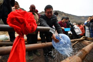 Villagers fill water bottles from a 400-metre-deep well in northern China (Image: Alamy)