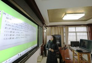 A middle school teacher in south China gives a lesson to an empty classroom via internet. Students remain isolated at home as part of efforts to prevent the spread of the coronavirus. (Image: Alamy)