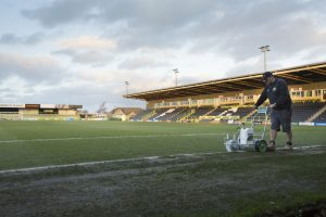 Forest Green's groundsman Adam Witchell marks the byline before a match (Image: Chris Davy/China Dialogue)