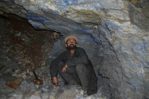 A miner looking at lapis lazuli veins inside a mine.