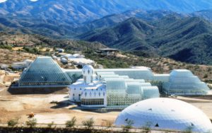 "The Biosphere 2 facility in southern Arizona. The white domed structure is one of two ""lungs"" (expansion chambers) connected to the main structure by air tunnels. In the distance is the Biospheric Research and Development complex where much of the initial system research, training for participants, and raising of plants, animals and insects occurred. Biosphere 2 included 30,000 tonnes of soil, 3800 species of plants and animals, and eight humans (Image: Gill C Kenny)."
