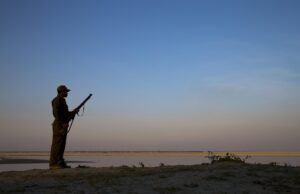 An armed forest guard looking out over the Brahmaputra River