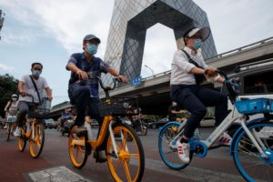 People ride shared bicycles past the CCTV headquarters in the Central Business District following an outbreak of the coronavirus disease (COVID-19) in Beijing, China, August 4, 2020. Picture taken August 4, 2020