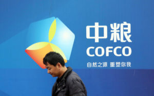 A pedestrian walks past a billboard of COFCO (China National Cereals, Oils and Foodstuffs Corporation)