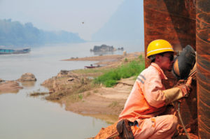 A Chinese welder at work on a bridge over the Mekong, part of the China–Laos high-speed railway