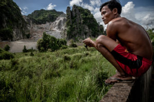 Villager Nuon Oun watches as limestone rock is quarried from the side of Phnom La'ang, a karst mountain in southern Cambodia (Image: Roun Ry / China Dialogue)