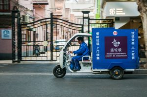 An electric tuktuk transporting household food waste zips past houses on Shanghai's Jiaozhou Road. (Image: Mark Andrews / Alamy )