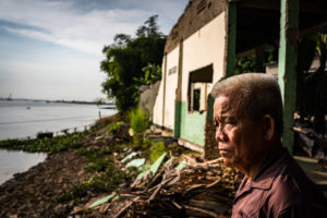 Nguyen Van Thuong, 71 stands in front of his former neighbors house which has been destroyed and fallen into the river as a result of erosion