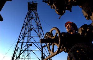 An oil worker repairs a pipe on an oil field in the Caspian Sea in petrostate Azerbaijan