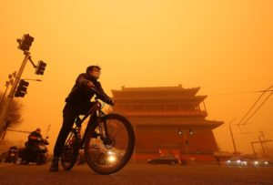 Chinese cycle past a temple shrouded under a thick sandstorm in Beijing on Monday, March 15, 2021