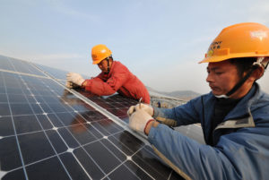 Chinese workers install solar panels at a photovoltaic (PV) power plant in Xiji town, Zaozhuang city