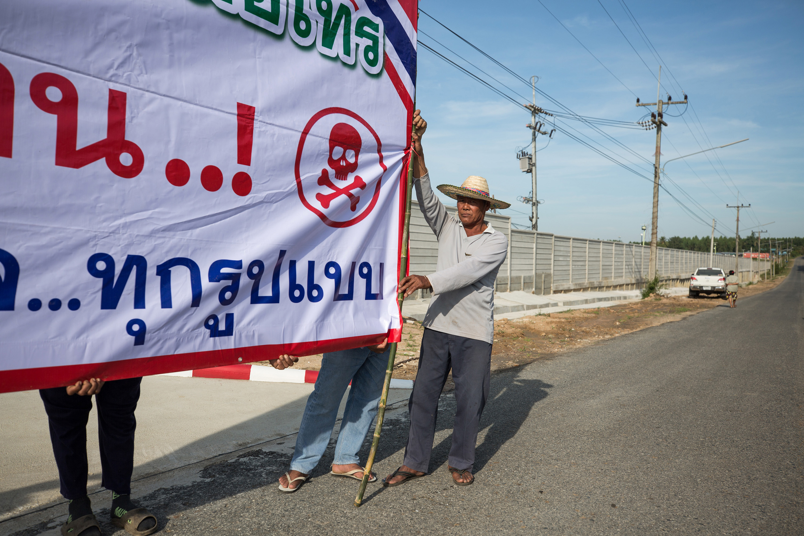 Local villagers in Bo Thong, Chonburi, protest with banners outside the industrial state that plans to become a recycling plant for plastics.