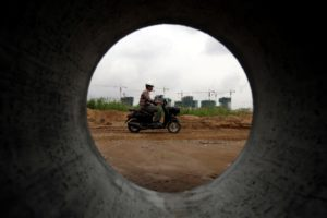Phnom Penh special economic zone, man rides a motorbike at a construction site