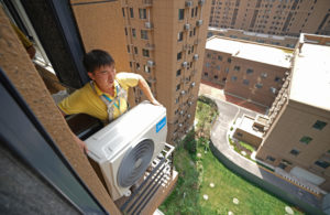 man installs an air conditioner, which produces HFCs