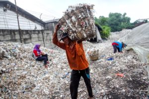 People collect plastic scraps and paper to take to a local factory in Indonesia