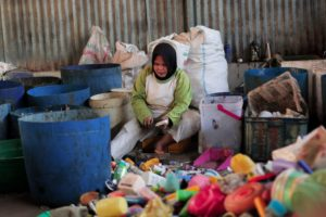 A waste collector in Indonesia, sorts through household waste to find recyclable plastics