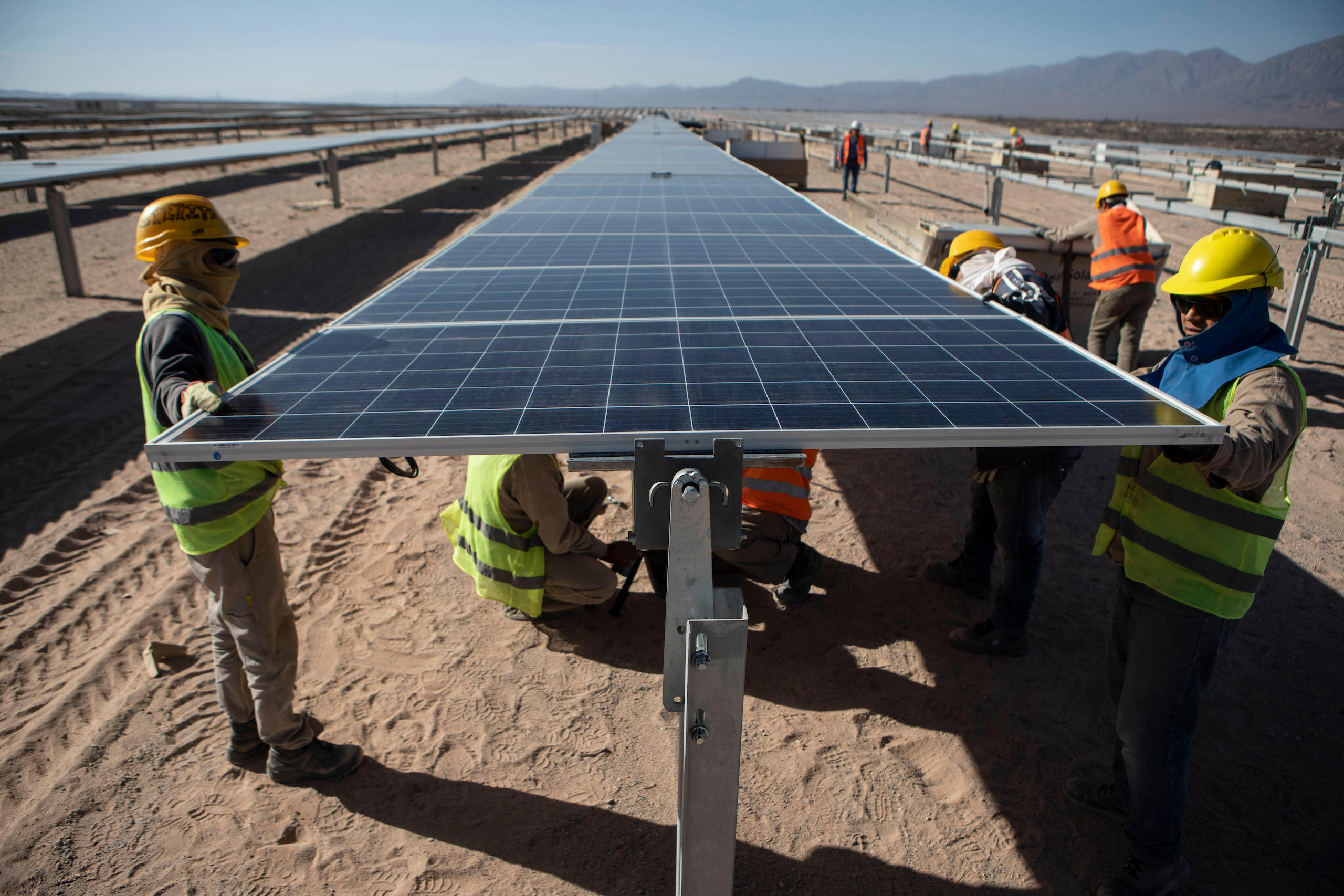 workers install solar panels argentina